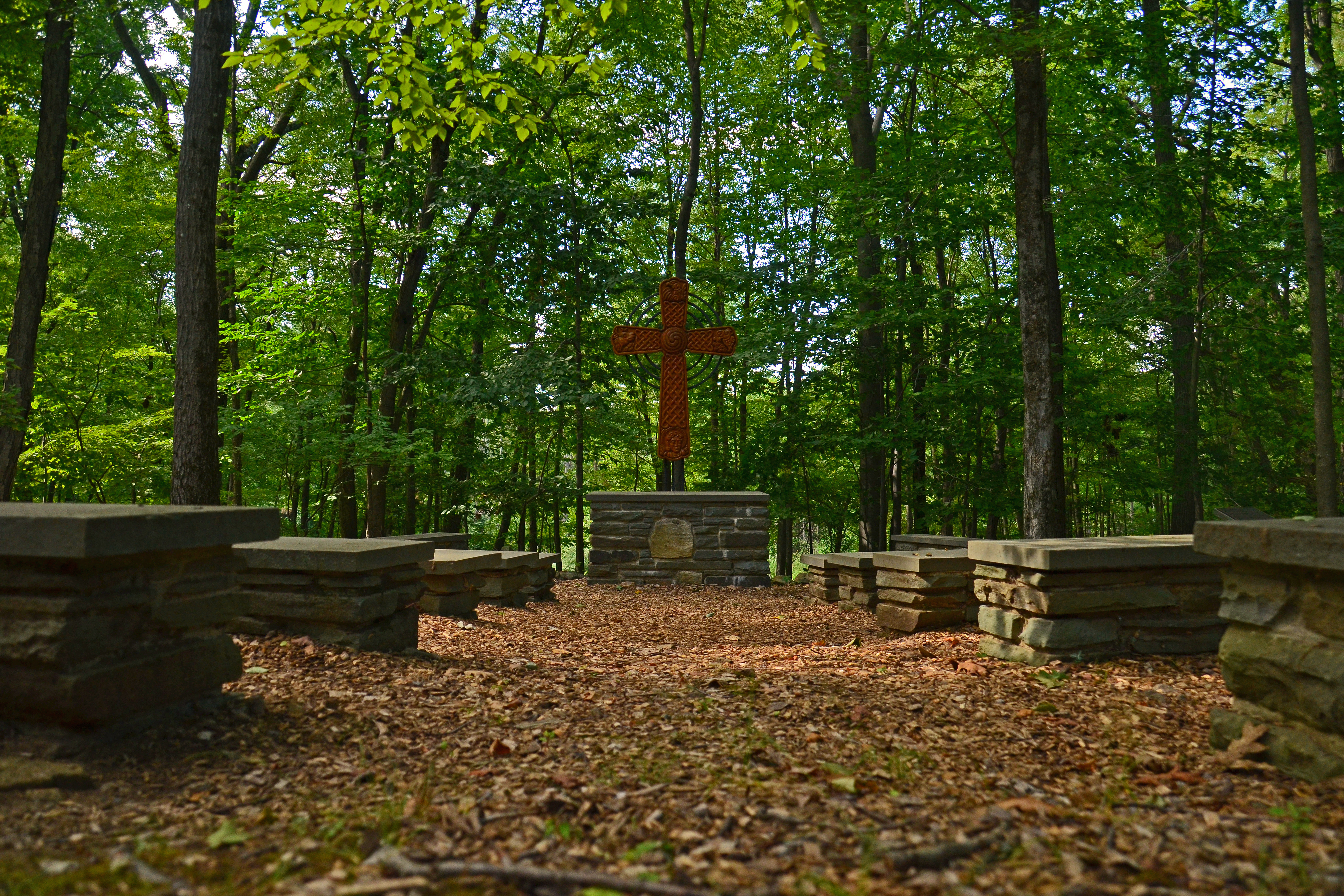 picture of outdoor chapel with stone benches and carved wooden cross